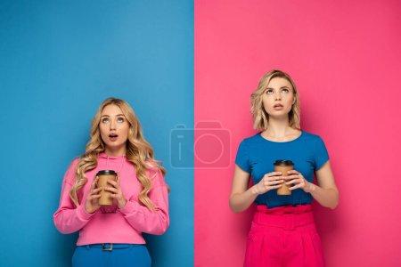 Photo pour Sœurs blondes choquées avec des tasses jetables regardant vers le haut sur fond rose et bleu - image libre de droit