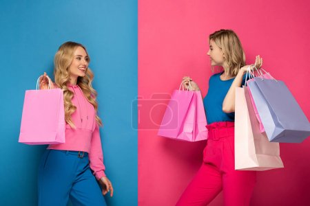 Photo for Attractive blonde sisters holding shopping bags and smiling at each other on pink and blue background - Royalty Free Image