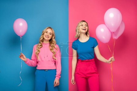 Photo for Cheerful blonde girls holding balloons on blue and pink background - Royalty Free Image
