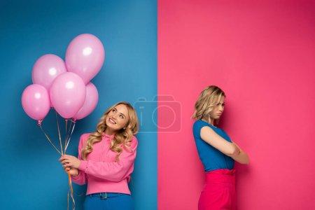 Photo pour Fille blonde souriante tenant des ballons près de sœur triste avec les bras croisés sur fond bleu et rose - image libre de droit