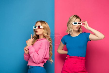 Photo for Attractive blonde sisters in 3d glasses on blue and pink background - Royalty Free Image