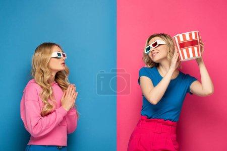 Photo pour Fille blonde dans des lunettes 3D avec des mains de prière près de soeur blonde souriante tenant du pop-corn sur fond bleu et rose - image libre de droit