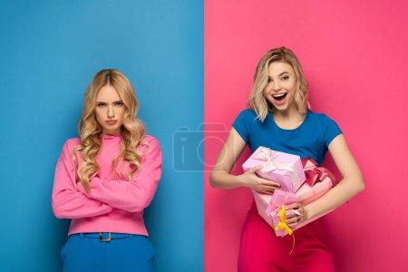 Photo pour Fille gaie tenant des boîtes-cadeaux près offensé soeur blonde sur fond bleu et rose - image libre de droit