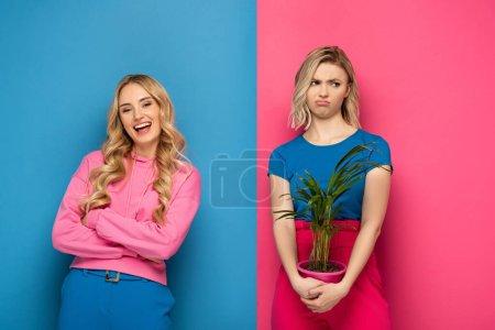 Photo pour Fille souriante regardant caméra près triste soeur blonde avec plante sur fond rose et bleu - image libre de droit