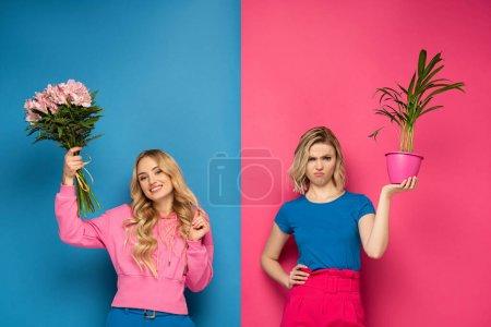 Photo pour Fille souriante tenant bouquet près offensé soeur avec plante sur fond rose et bleu - image libre de droit