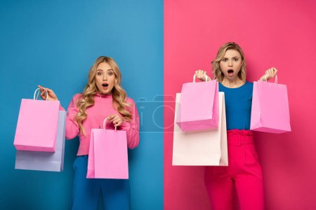 Photo pour Surprised blonde salope sisters with shopping bags looking at camera on pink and blue background - image libre de droit