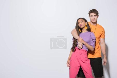 Photo pour Beau gars embrassant la petite amie afro-américaine à la mode tout en regardant la caméra sur fond blanc - image libre de droit