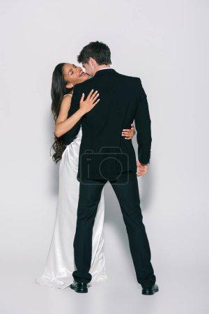 Photo pour Vue d'ensemble d'une mariée américaine africaine heureuse embrassant un marié élégant sur fond blanc - image libre de droit