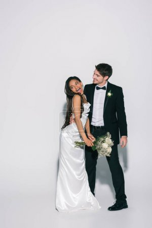 full length view of elegant bridegroom hugging happy african american bride holding wedding bouquet on white background