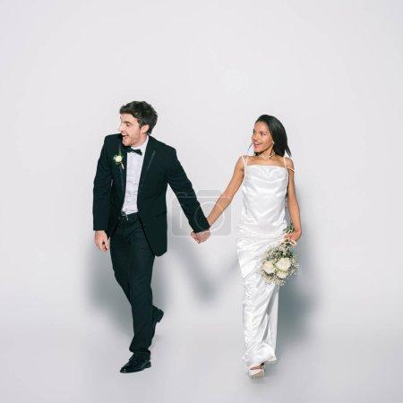 Photo pour Vue pleine longueur de jeunes mariés interraciaux souriants et élégants tenant la main tout en marchant et regardant loin sur fond blanc - image libre de droit