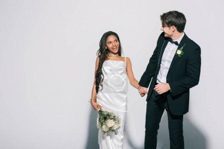 Photo pour Mariée élégante tenant la main de la mariée africaine américaine heureuse avec bouquet de mariage sur fond blanc - image libre de droit
