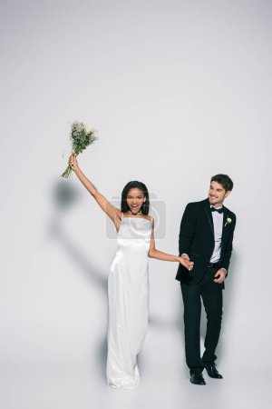 full length view of happy african american bride holding wedding bouquet in raised hand while holding hands with elegant bridegroom on white background