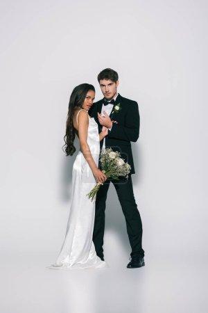 Photo pour Vue d'ensemble de la mariée élégante et de la jolie mariée africaine américaine regardant la caméra tout en posant sur fond blanc - image libre de droit