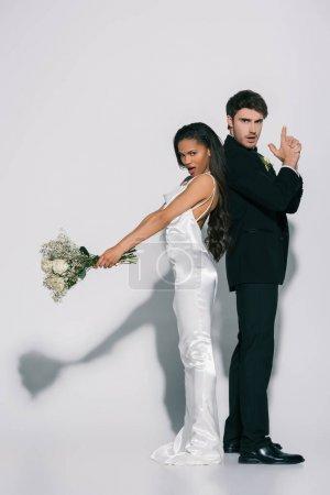 Photo pour Vue d'ensemble d'un marié confiant montrant un geste de tir tout en se tenant debout dos à dos avec une épouse africaine américaine avec un bouquet de mariage sur fond blanc - image libre de droit
