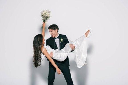 Photo pour Marié excité tenant heureuse mariée afro-américaine sur les mains sur fond blanc - image libre de droit