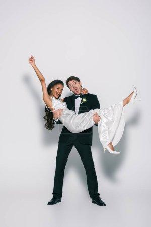 Photo pour Pleine longueur vue d'une mariée joyeuse tenant une fiancée africaine d'Amérique sur les mains sur fond blanc - image libre de droit