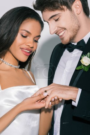 Photo for Beautiful african american bride putting wedding ring on finger of happy groom on white background - Royalty Free Image