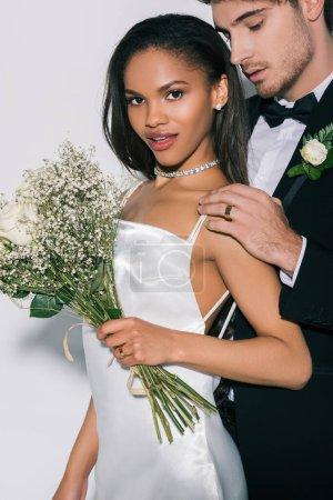 """Photo pour Belle fille africaine américaine avec un bouquet de mariage regardant la caméra alors que le marié se touche l """"épaule sur fond blanc - image libre de droit"""