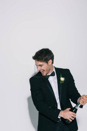 Photo pour Marié excité avec les yeux fermés ouvrant bouteille de champagne sur fond blanc - image libre de droit