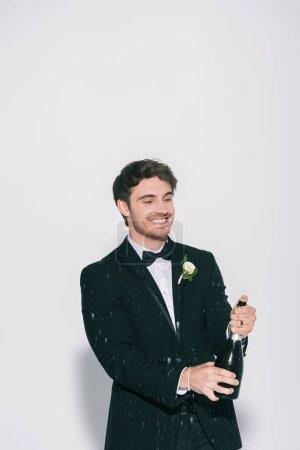 joyeuse bouteille d'ouverture marié près des éclaboussures de champagne sur fond blanc