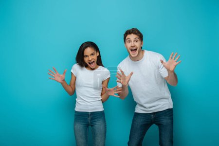 Photo for Cheerful interracial couple showing frightening gestures at camera on blue background - Royalty Free Image