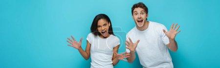 Photo pour Plan panoramique de joyeux couple interracial montrant des gestes effrayants à la caméra sur fond bleu - image libre de droit