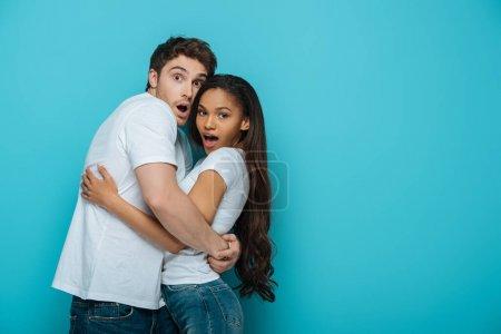 Photo pour Couple interracial effrayé embrasser et regarder la caméra sur fond bleu - image libre de droit