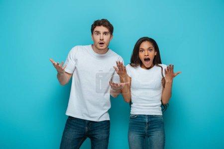 Photo pour Choqué couple interracial debout avec les bras ouverts tout en regardant la caméra sur fond bleu - image libre de droit