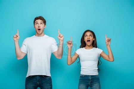Foto de Impactada pareja interracial mirando hacia arriba y señalando con los dedos sobre fondo azul - Imagen libre de derechos