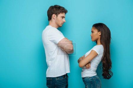Photo pour Vue latérale du couple interracial offensé debout avec les bras croisés et se regardant sur fond bleu - image libre de droit