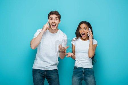 Photo pour Excité couple interracial parler sur les smartphones tout en se tenant les bras ouverts sur fond bleu - image libre de droit