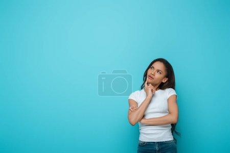 nachdenkliches afrikanisch-amerikanisches Mädchen berührt Kinn beim Wegschauen isoliert auf blau