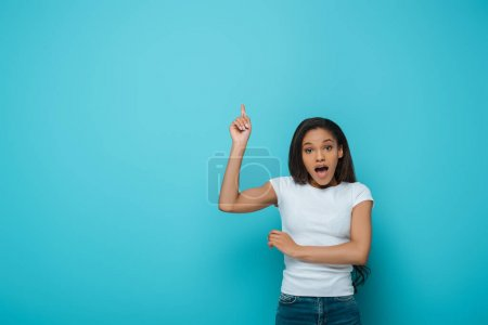 Photo for Shocked african american girl looking at camera while pointing up with finger on blue background - Royalty Free Image