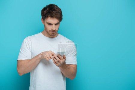 Photo pour Jeune homme concentré à l'aide d'un smartphone sur fond bleu - image libre de droit