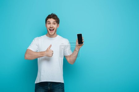 Photo for Excited young man showing thumb up while holding smartphone with blank screen on blue background - Royalty Free Image