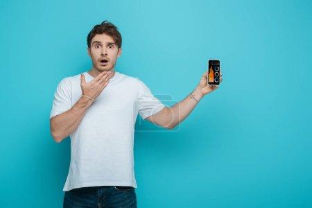 Photo pour Choqué gars tenant la main près du visage tout en montrant smartphone avec l'application d'analyse d'entreprise sur fond bleu - image libre de droit