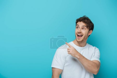 Photo for Surprised guy looking away and pointing with finger on blue background - Royalty Free Image