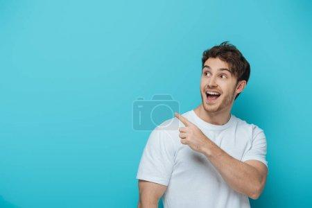 Photo pour Surpris gars regardant loin et pointant du doigt sur fond bleu - image libre de droit