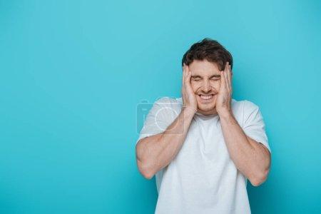 Photo pour Effrayé jeune homme toucher le visage tout en grimaçant avec les yeux fermés sur fond bleu - image libre de droit