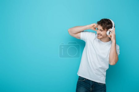 Photo for Excited young man touching wireless headphones while listening music with closed eyes on blue background - Royalty Free Image