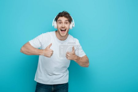 excited young man in wireless headphones showing thumbs up while looking at camera on blue background