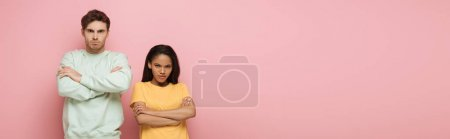 Photo for Horizontal image of offended interracial couple standing with crossed arms while looking at camera on pink background - Royalty Free Image