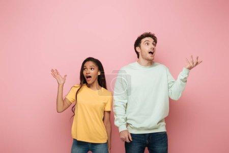 Photo pour Choqué couple interracial debout avec les bras ouverts tout en regardant loin sur fond rose - image libre de droit