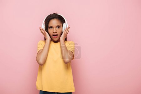 Photo for Shocked african american girl touching wireless headphones while looking at camera on pink background - Royalty Free Image