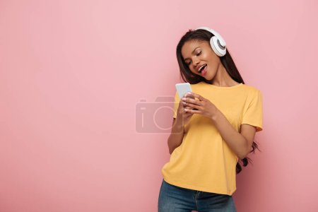 Photo for Happy african american girl in wireless headphones chatting on smartphone on pink background - Royalty Free Image