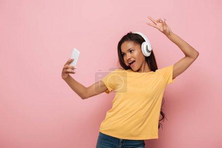 Photo pour Heureux afro-américaine fille dans les écouteurs sans fil prendre selfie sur smartphone tout en montrant signe de victoire sur fond rose - image libre de droit