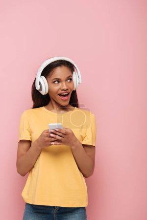 Photo for Cheerful african american girl in wireless headphones using smartphone while looking away on pink background - Royalty Free Image