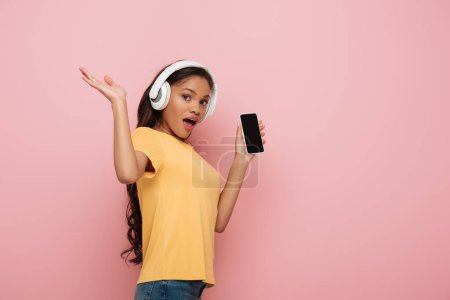 excited african american girl in wireless headphones showing smartphone with blank screen on pink background