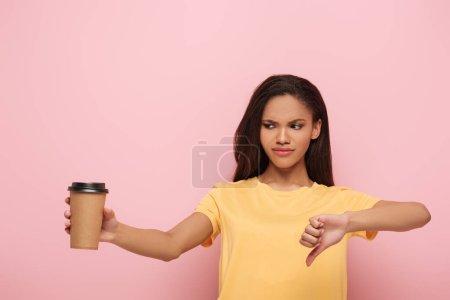 Photo pour Mécontent afro-américaine fille montrant pouce vers le bas tout en tenant du café pour aller sur fond rose - image libre de droit