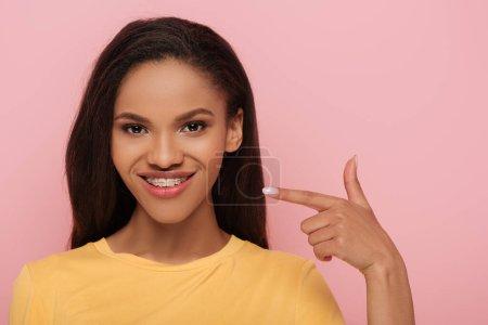Photo pour Une Africaine américaine souriante pointant avec un doigt vers l'appareil dentaire de ses dents isolées en rose - image libre de droit